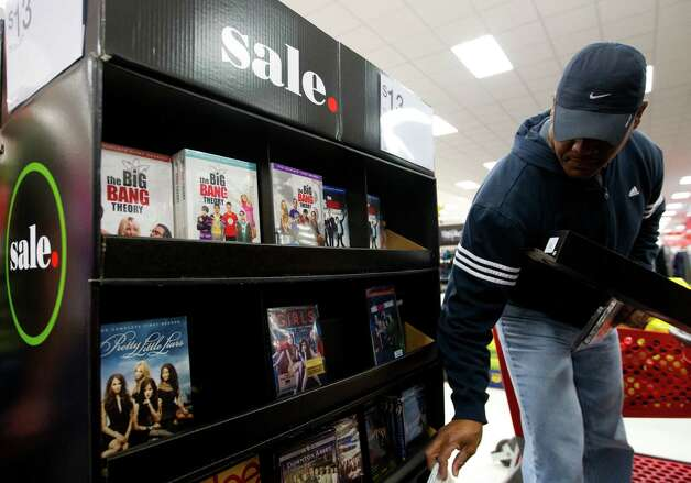 """Billy Rivers looks at movies on sale at Target during Black Friday, Nov. 29, 2013, in Houston. """"I'm enjoying them for whatever I need,"""" he said of the sales. """"I need to look for a few more things and hopefully get a good price on those."""" (Cody Duty / Houston Chronicle) Photo: Cody Duty, Staff / © 2013 Houston Chronicle"""