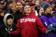 Cougar's fan Paul Moorhead, center, reacts to a call in favor of the Huskies during the 106th annual Apple Cup Friday, Nov. 29, 2013, at Husky Stadium in Seattle. The Huskies beat the Cougars 27-17.