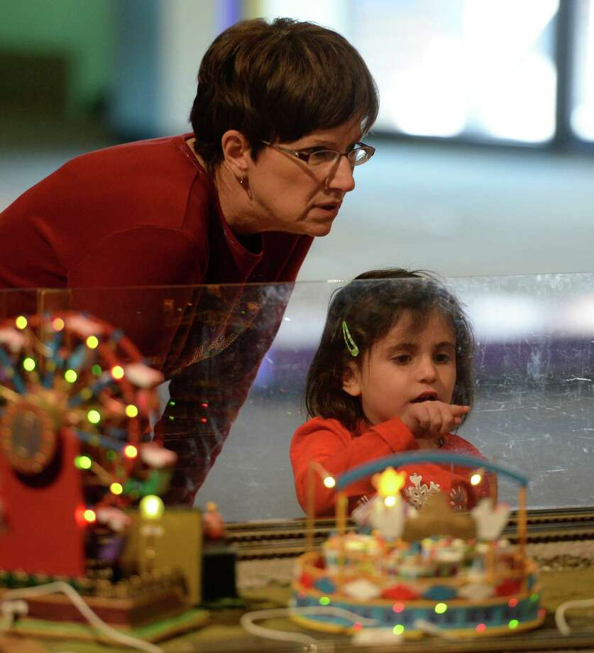 Grandparent Linda Shannon joins granddaughter Kylie Shannon, 4, as she watches the trains circulate the layout during the opening of the annual Model Train exhibit at the miSci Nov. 29, 2013 in Schenectady, N.Y.    (Skip Dickstein/Times Union) Photo: SKIP DICKSTEIN / 00024830A