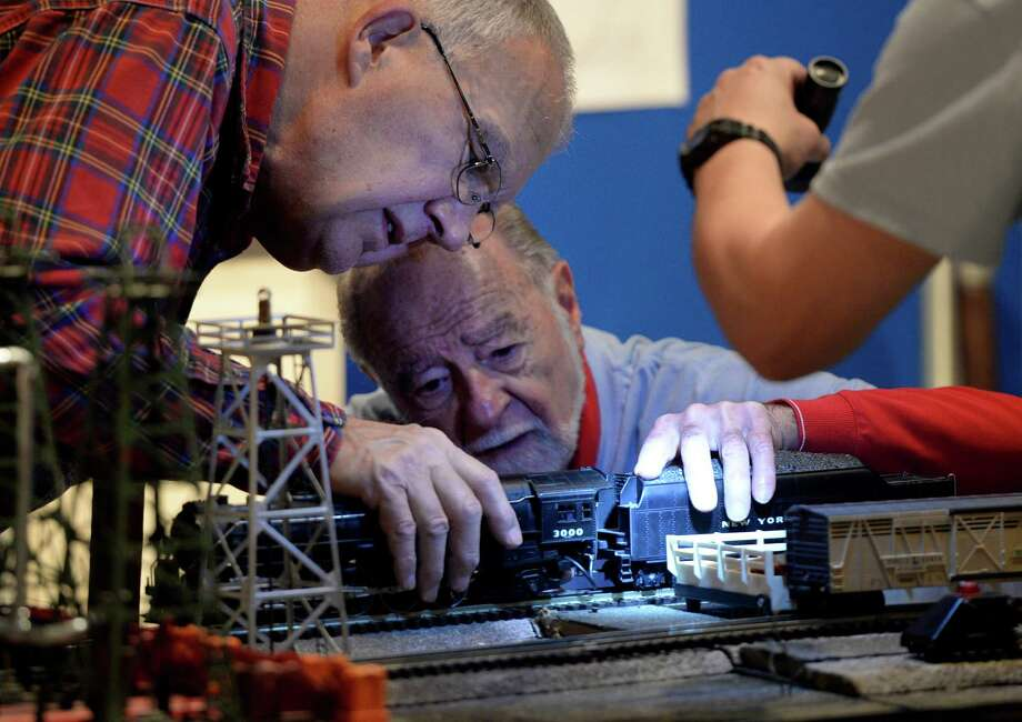Model train master Dave Acker, left, gets an assist from volunteer Bob Fopeano as the  try to diagnose a derailment during the opening day of the annual Model Train exhibit at the miSci Nov. 29, 2013 in Schenectady, N.Y.    (Skip Dickstein/Times Union) Photo: SKIP DICKSTEIN / 00024830A