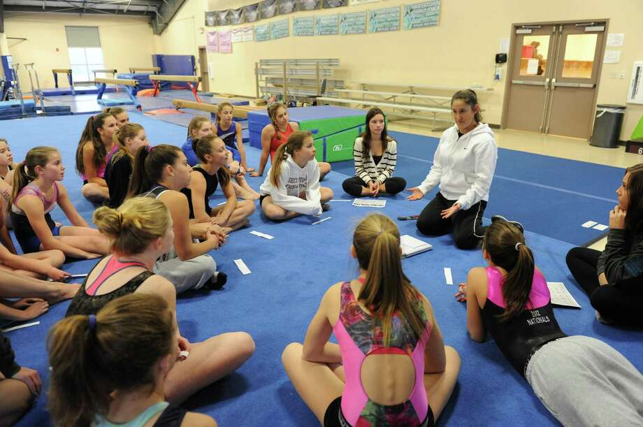 Saratoga Springs High School gymnastics head coach Deb Smarro works with her team during practice on Tuesday Nov. 26, 2013 in Saratoga Springs, N.Y. (Michael P. Farrell/Times Union) Photo: Michael P. Farrell / 00024786A