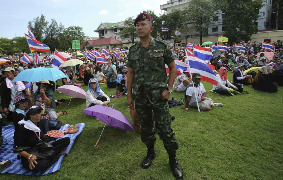 A Thai soldier stands as anti-government protesters sit at the Royal Thai army compound in Bangkok after demonstrators stormed the facility. Photo: Sakchai Lalit / Associated Press