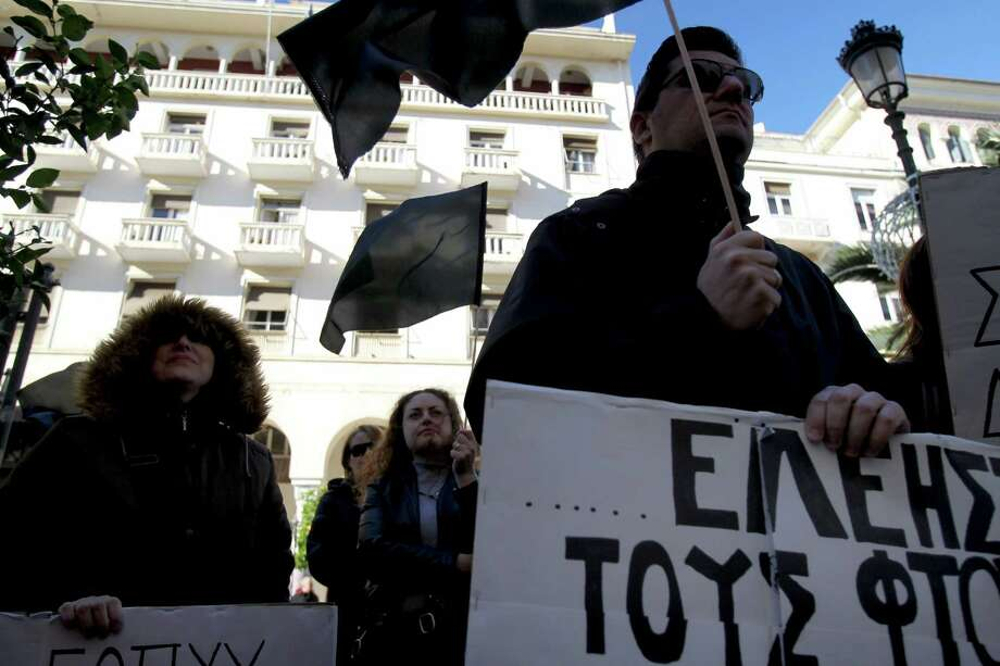 """A demonstrator holds a flag and a placard that reads in Greek """"Solidarity to the P??r"""", during a protest outside the Health Ministry office in the northern Greek port city of Thessaloniki, Friday, Nov. 29, 2013. Greek state hospitals are functioning with emergency staff as doctors and staff hold a 24-hour strike against planned health cutbacks enforced under the country's harsh austerity program. Unions are angry at the conservative-led government's plans to suspend and reallocate staff as part of its drive to reform the public sector and reduce the budget deficit. (AP Photo/Nikolas Giakoumidis) ORG XMIT: XNG102 Photo: Nikolas Giakoumidis / AP"""