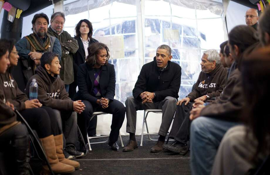President Barack Obama and first lady Michelle Obama visit with individuals at the National Mall who have been fasting since Nov. 12 to protest House inaction on immigration legislation. Photo: Pablo Martinez Monsivais / Associated Press