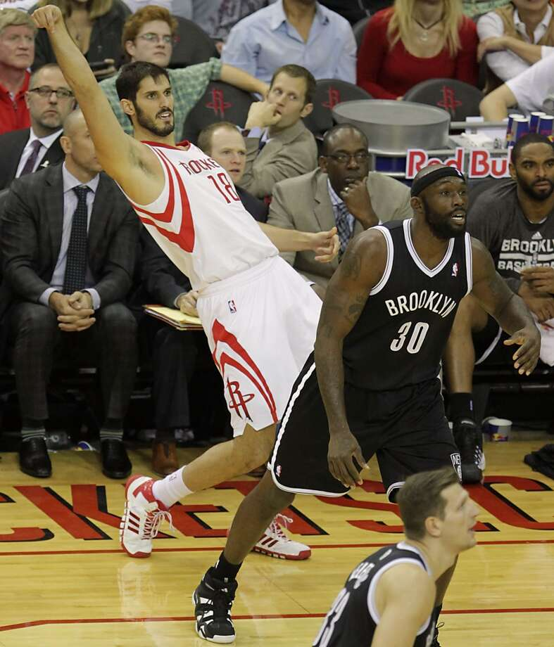 Rockets small forward Omri Casspi  left, watches as his three fall into the basket. Photo: James Nielsen, Houston Chronicle