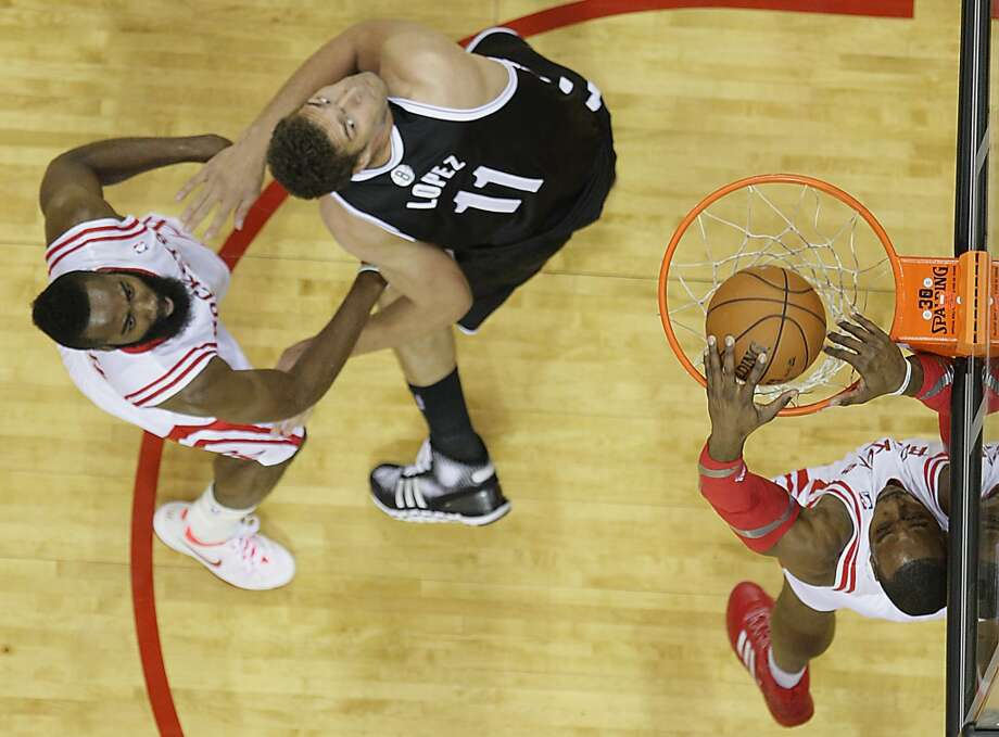 Rockets power forward Dwight Howard dunks the ball as Rockets shooting guard James Harden left, and Nets center Brook Lopez center, look on. Photo: James Nielsen, Houston Chronicle