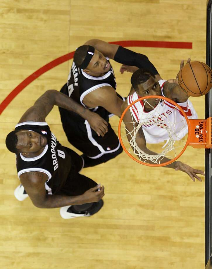 Rockets power forward Terrence Jones right, watches his shot fall into the basket as Nets center Andray Blatche left, and Nets small forward Paul Pierce center, look on. Photo: James Nielsen, Houston Chronicle