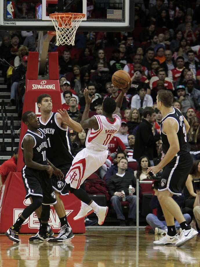 Rockets point guard Aaron Brooks, 2nd from right, scores a shot as the Tyshawn Taylor left, Brook Lopez, 2nd from left, and Mirza Teletovic look on. Photo: James Nielsen, Houston Chronicle