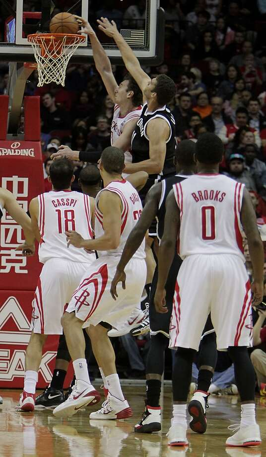 Rockets center Omer Asik upper left, dunks the ball past Nets center Brook Lopez. Photo: James Nielsen, Houston Chronicle