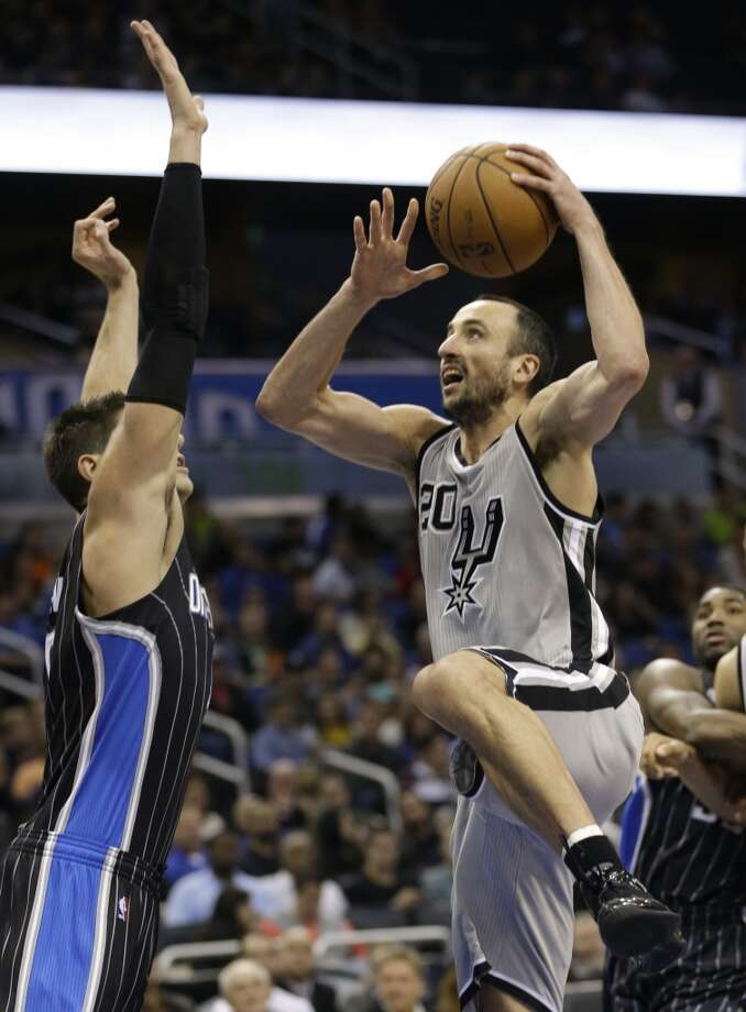 San Antonio Spurs' Manu Ginobili, right, of Argentina, takes a shot over Orlando Magic's Nikola Vucevic, of Montenegro, during the second half of an NBA basketball game in Orlando, Fla., Friday, Nov. 29, 2013. San Antonio Spurs won the game 109-91.(AP Photo/John Raoux) Photo: Associated Press