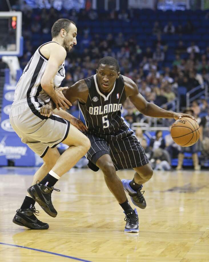 Orlando Magic's Victor Oladipo (5) drives around San Antonio Spurs' Manu Ginobili, left, of Argentina, during the first half of an NBA basketball game in Orlando, Fla., Friday, Nov. 29, 2013.(AP Photo/John Raoux) Photo: Associated Press