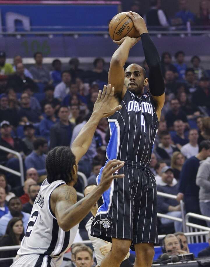 Orlando Magic's Arron Afflalo (4) takes a shot over San Antonio Spurs' Kawhi Leonard (2) during the first half of an NBA basketball game in Orlando, Fla., Friday, Nov. 29, 2013.(AP Photo/John Raoux) Photo: Associated Press