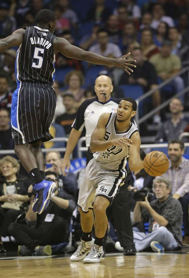 San Antonio Spurs' Cory Joseph (5) passes the ball around Orlando Magic's Victor Oladipo (5) during the first half of an NBA basketball game in Orlando, Fla., Friday, Nov. 29, 2013.(AP Photo/John Raoux) Photo: Associated Press