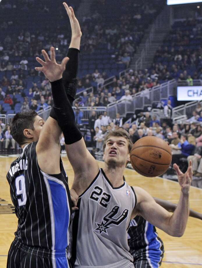 San Antonio Spurs' Tiago Splitter (22), of Brazil, loses the ball as he goes up for a shot against Orlando Magic's Nikola Vucevic (9), of Montenegro, during the first half of an NBA basketball game in Orlando, Fla., Friday, Nov. 29, 2013. (AP Photo/John Raoux) Photo: Associated Press