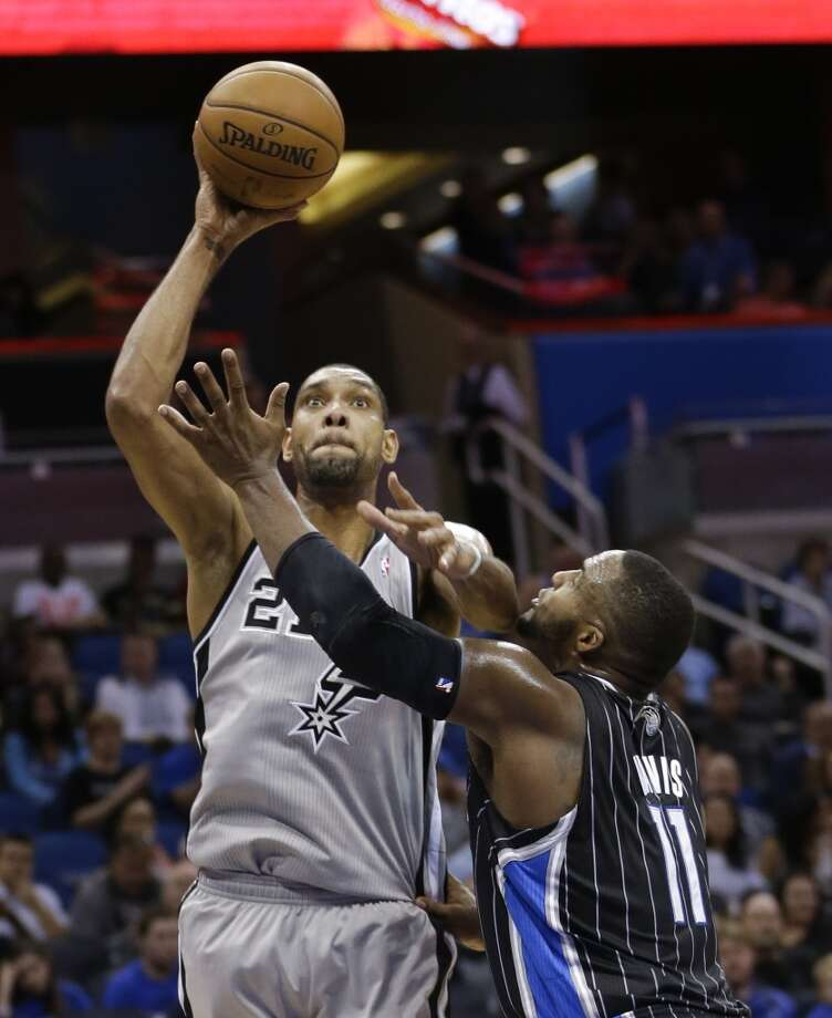 San Antonio Spurs' Tim Duncan, left, makes a shot over Orlando Magic's Glen Davis (11) during the second half of an NBA basketball game in Orlando, Fla., Friday, Nov. 29, 2013. San Antonio won 109-91.(AP Photo/John Raoux) Photo: Associated Press