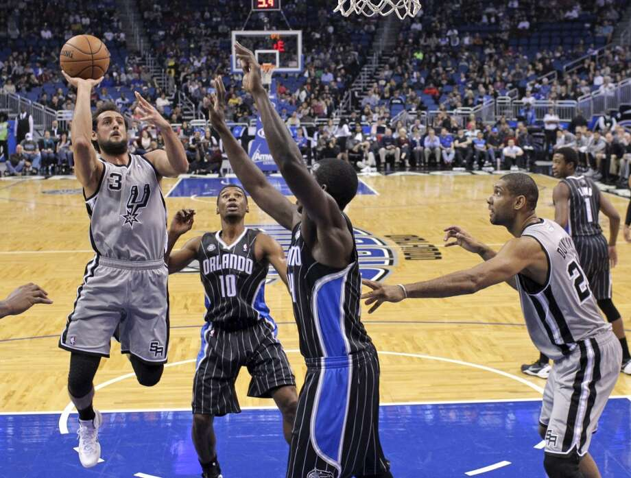 San Antonio Spurs' Marco Belinelli (3), of Italy, goes up for a shot past Orlando Magic's Ronnie Price (10), Andrew Nicholson, center, as teammate Tim Duncan, right, looks on, during the first half of an NBA basketball game in Orlando, Fla., Friday, Nov. 29, 2013.(AP Photo/John Raoux) Photo: Associated Press