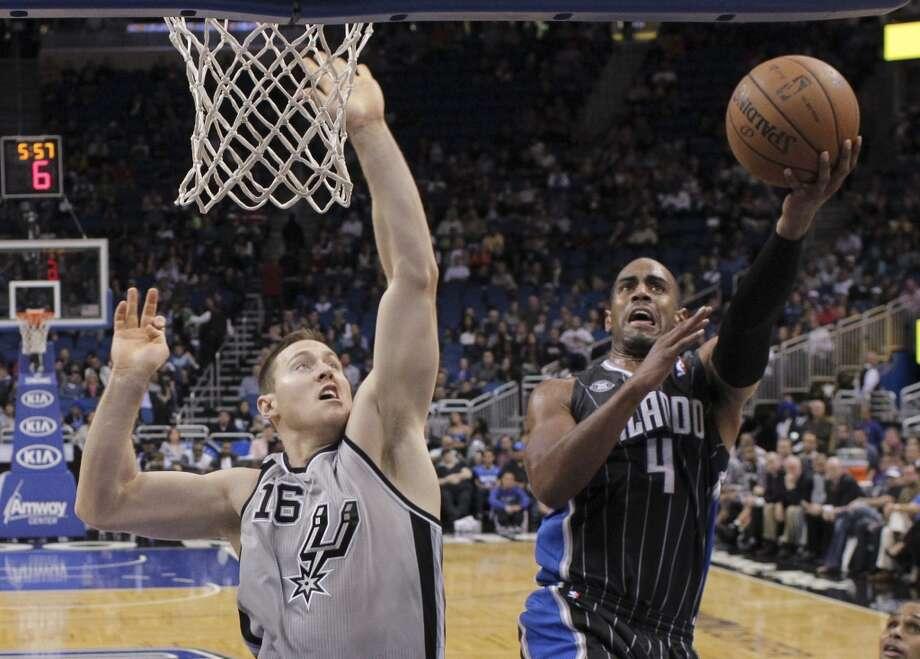 Orlando Magic's Arron Afflalo (4) gets past San Antonio Spurs' Aron Baynes (16) for a shot during the second half of an NBA basketball game in Orlando, Fla., Friday, Nov. 29, 2013. The Spurs won 109-91.(AP Photo/John Raoux) Photo: Associated Press