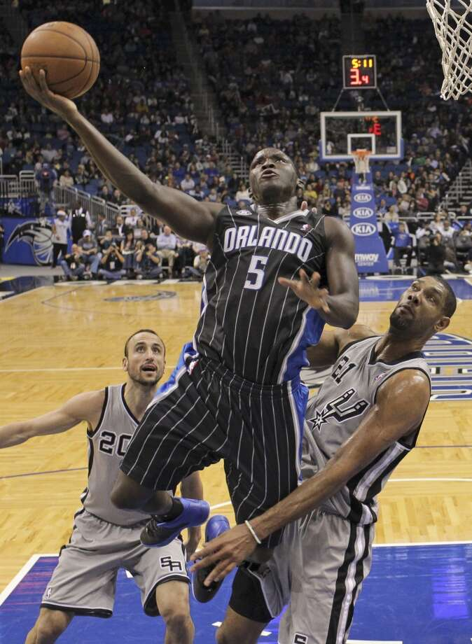 Orlando Magic's Victor Oladipo (5) makes a shot as he gets between San Antonio Spurs' Tim Duncan (21) and Manu Ginobili (20), of Argentina, during the second half of an NBA basketball game in Orlando, Fla., Friday, Nov. 29, 2013. The Spurs won 109-91.(AP Photo/John Raoux) Photo: Associated Press