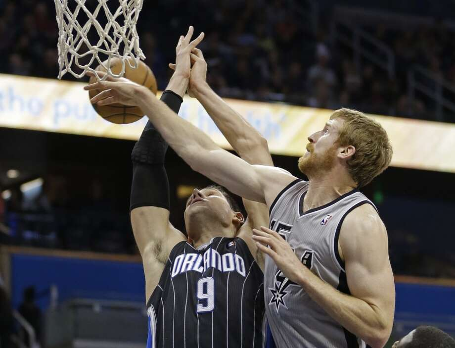 Orlando Magic's Nikola Vucevic (9), of Montenegro, goes after a rebound against San Antonio Spurs' Matt Bonner during the second half of an NBA basketball game in Orlando, Fla., Friday, Nov. 29, 2013. San Antonio Spurs won the game 109-91.(AP Photo/John Raoux) Photo: Associated Press