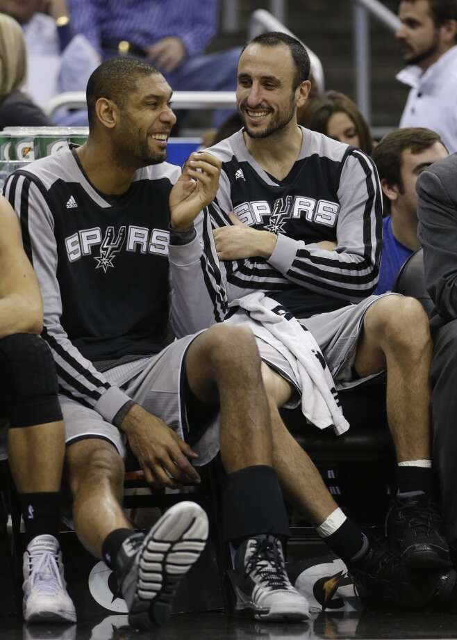 San Antonio Spurs' Tim Duncan, left, and Manu Ginobili joke around as they relax on the bench during the second half of an NBA basketball game against the Orlando Magic in Orlando, Fla., Friday, Nov. 29, 2013. San Antonio Spurs won the game 109-91.(AP Photo/John Raoux) Photo: Associated Press