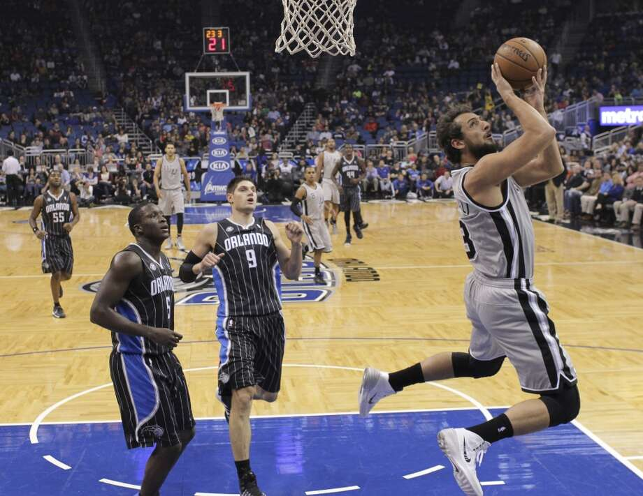 San Antonio Spurs' Marco Belinelli, right,  of Italy, spins as he takes a shot in front of Orlando Magic's Nikola Vucevic (9), of Montenegro, and Victor Oladipo (5)during the first half of an NBA basketball game in Orlando, Fla., Friday, Nov. 29, 2013.(AP Photo/John Raoux) Photo: Associated Press