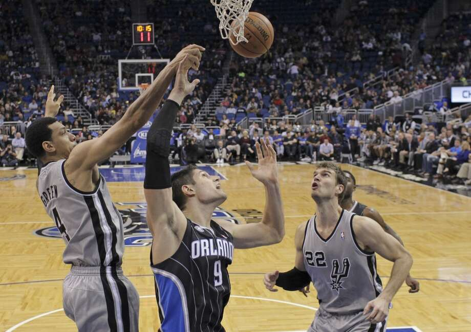 Orlando Magic's Nikola Vucevic (9), of Montenegro, goes after a rebound between San Antonio Spurs' Danny Green (4) and Tiago Splitter (22) during the second half of an NBA basketball game in Orlando, Fla., Friday, Nov. 29, 2013. San Antonio Spurs won the game 109-91.(AP Photo/John Raoux) Photo: Associated Press