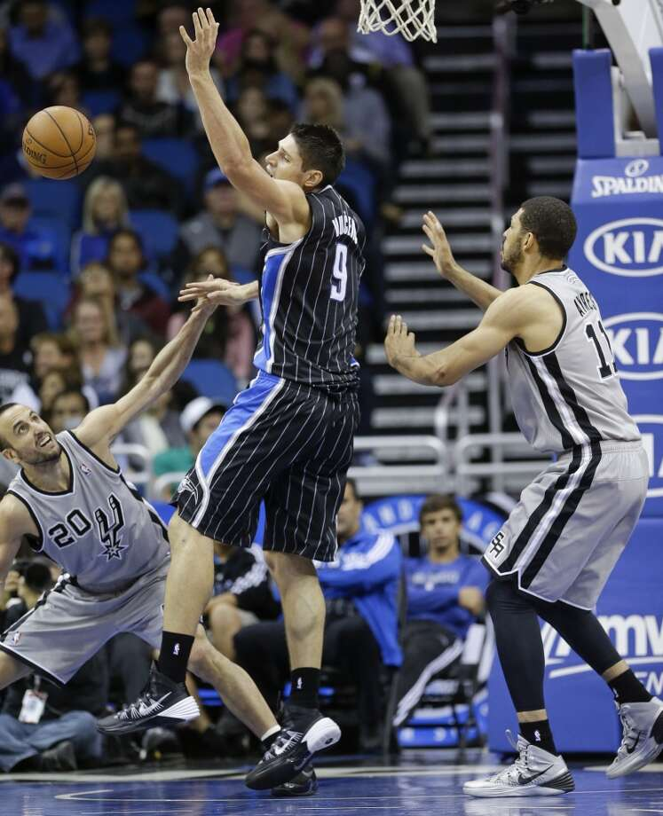 Orlando Magic's Nikola Vucevic (9), of Montenegro, loses the ball as he gets caught between San Antonio Spurs' Manu Ginobili (20), of Argentina, and Jeff Ayres (11) during the second half of an NBA basketball game in Orlando, Fla., Friday, Nov. 29, 2013. San Antonio Spurs won the game 109-91.(AP Photo/John Raoux) Photo: Associated Press