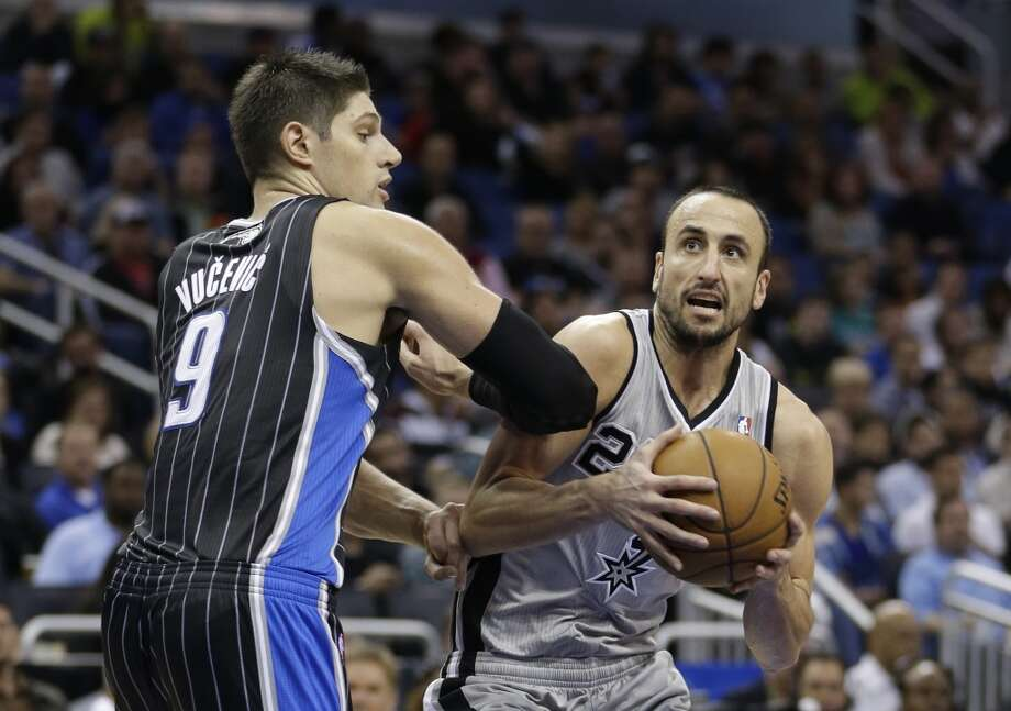 San Antonio Spurs' Manu Ginobili, right, of Argentina, goes up of a shot as he gets past Orlando Magic's Nikola Vucevic (9), of Montenegro, during the second half of an NBA basketball game in Orlando, Fla., Friday, Nov. 29, 2013. San Antonio Spurs won the game 109-91.(AP Photo/John Raoux) Photo: Associated Press