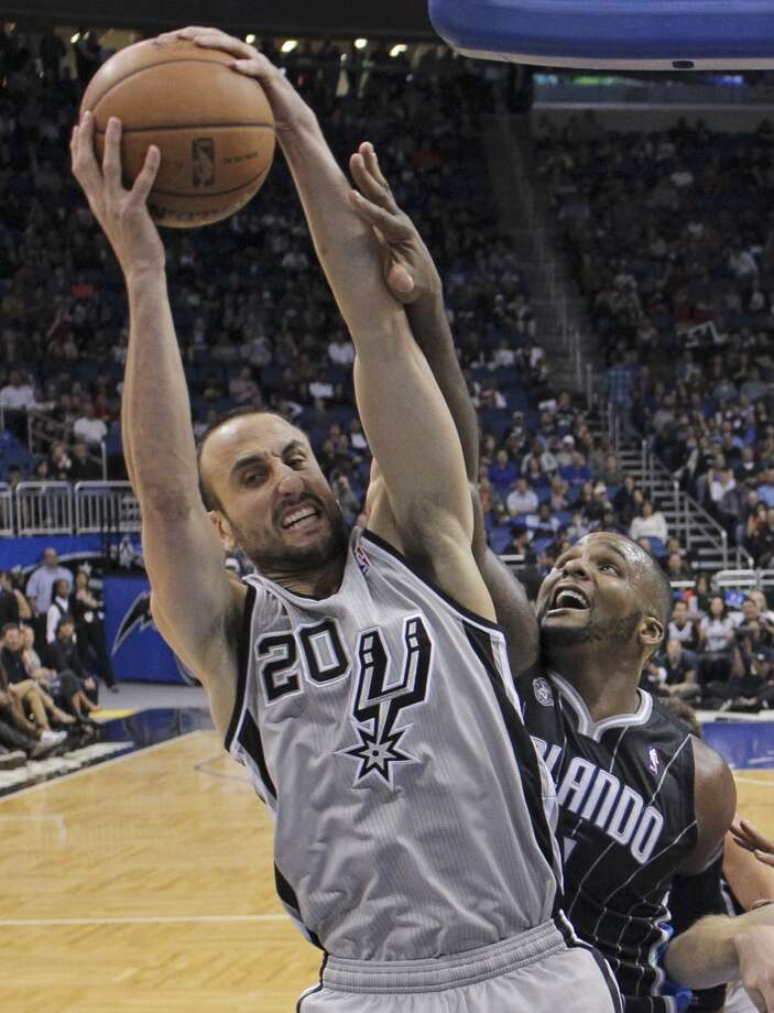 San Antonio Spurs' Manu Ginobili (20), of Argentina, grabs a rebound in front of Orlando Magic's Glen Davis during the second half of an NBA basketball game in Orlando, Fla., Friday, Nov. 29, 2013. San Antonio Spurs won the game 109-91.(AP Photo/John Raoux) Photo: Associated Press