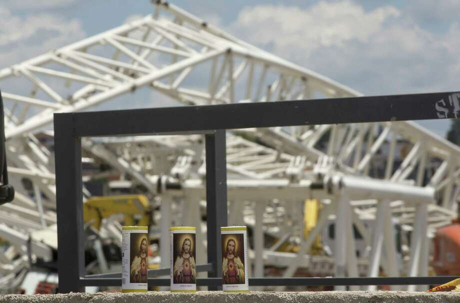 Candles sit on a wall Thursday near the metal structure that buckled at the Arena Corinthians in Sao Paulo. Wednesday's accident killed at least two workers when a construction crane collapsed. Photo: Andre Penner / Associated Press