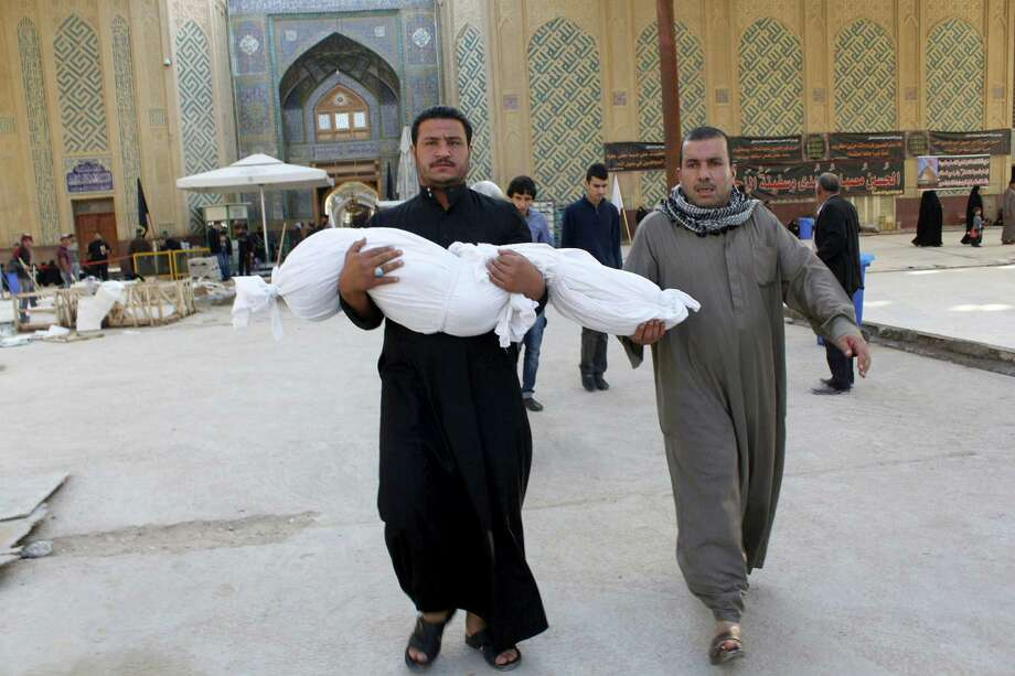 Reda Abdel Rahman carries the body of his 7-year-old son, Yasser, who was killed in a bombing Thursday, before burial Friday in the Shiite holy city of Najaf, 100 miles south of Baghdad. Photo: Jaber Al-Helo / Associated Press