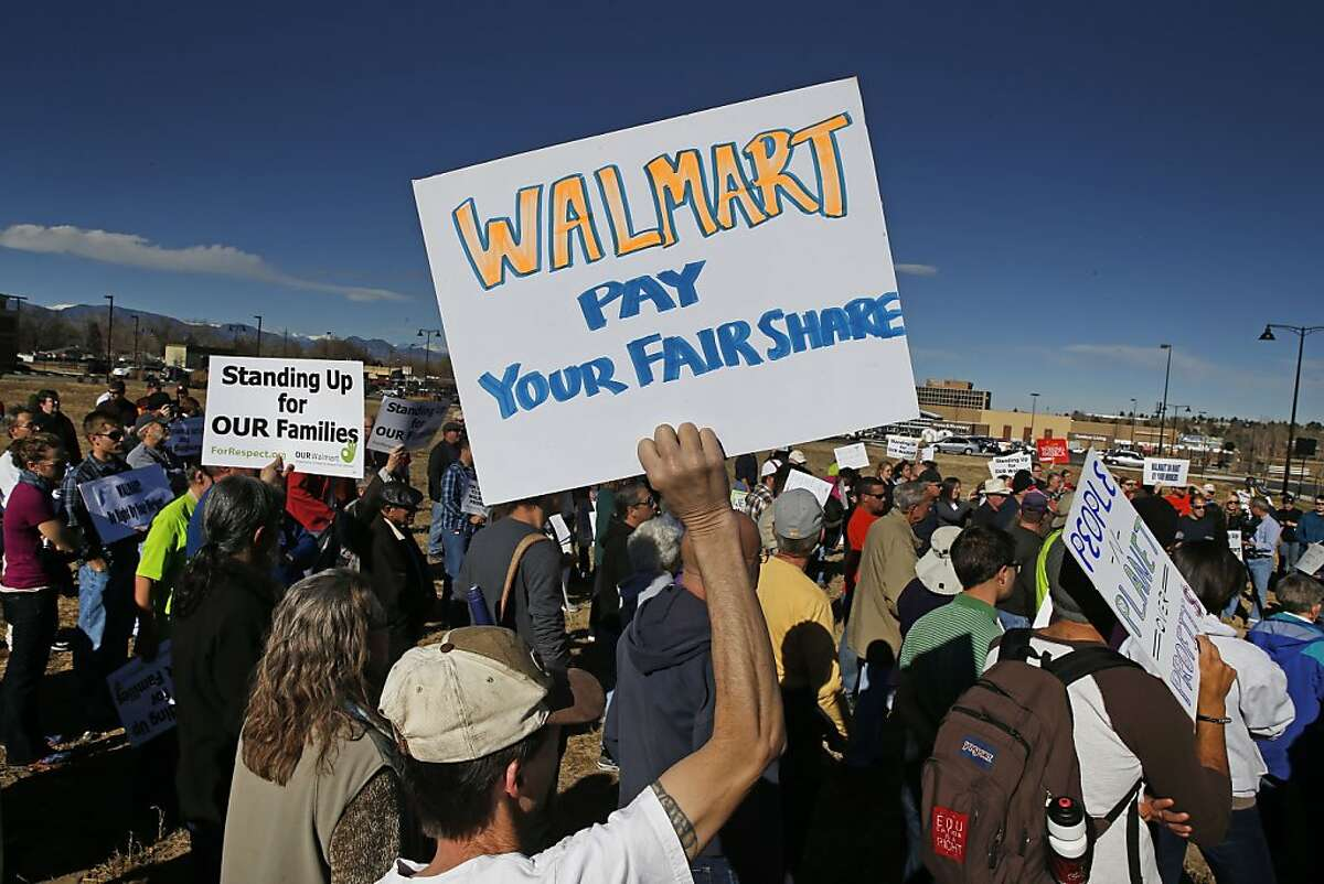 Colorado Walmart employees and supporters join nationwide protests, in front of a Walmart store in Lakewood, Colo., Friday, Nov. 29, 2013, for Walmart to publicly commit to improving labor standards. Black Friday, the day after Thanksgiving, is the nation's biggest shopping day of the year. (AP Photo/Brennan Linsley)