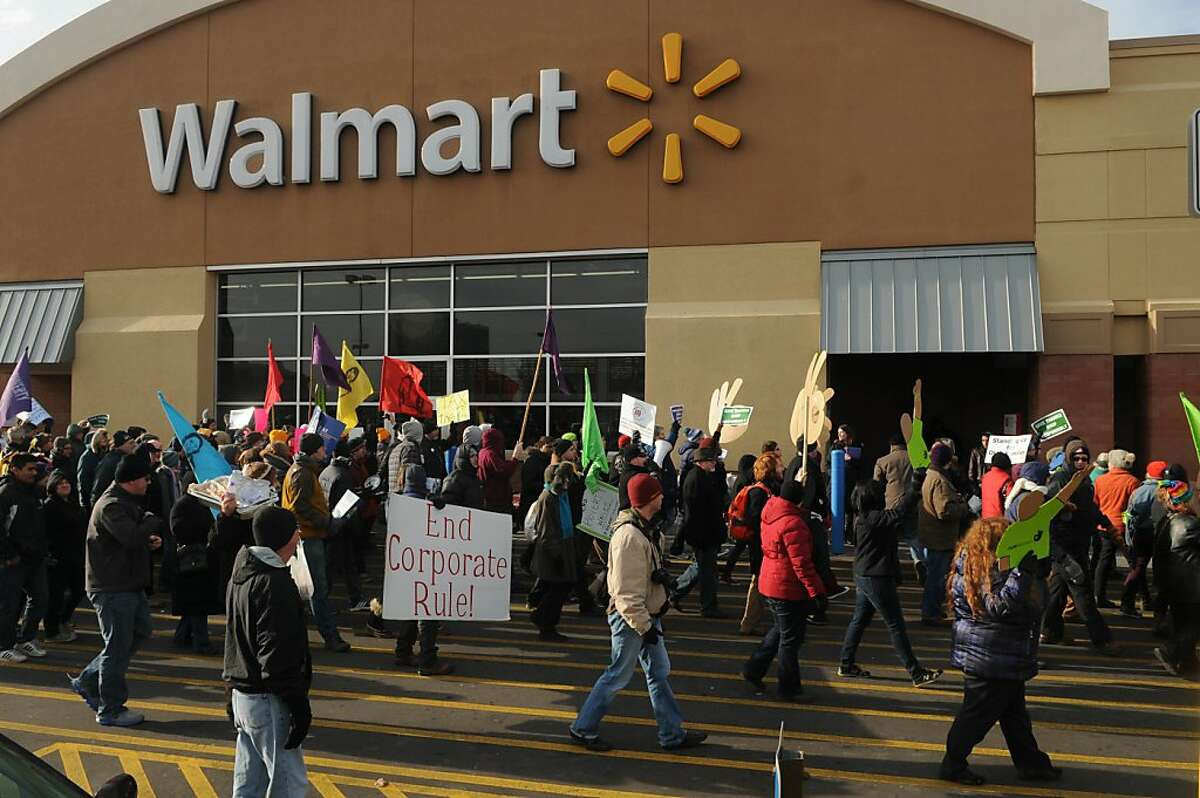 Protestors stream past the entrance to a Walmart store on Universty Avenue in St. Paul, Minn. on Black Friday, Nov. 29, 2013. On one of the busiest shopping days of the year, hundreds rallied to draw attention to low wages for retail workers and janitors. (AP Photo/Pioneer Press, Scott Takushi)