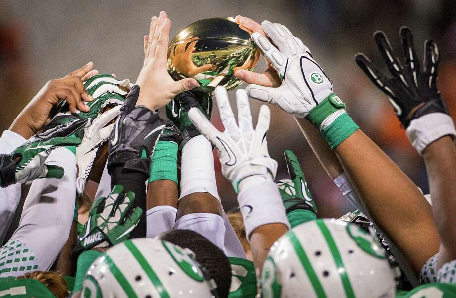 Brenham players celebrate with the trophy presented to the Class 4A Division II Regional Semifinal victors after a win over Texas City in high school football playoff game at the Berry Center Friday, Nov. 29, 2013, in Houston. Brenham won the game 37-34. Photo: Smiley N. Pool, Houston Chronicle / © 2013  Houston Chronicle