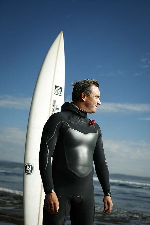 Elite surfer Shawn Dollar, 32, stands on a beach in Santa Cruz next to the surfboard he rode when he caught a world-record, 61-foot wave at the Cortes Bank, about 100 miles off the coast of San Diego. It was his second monster-wave record. Photo: Russell Yip, The Chronicle