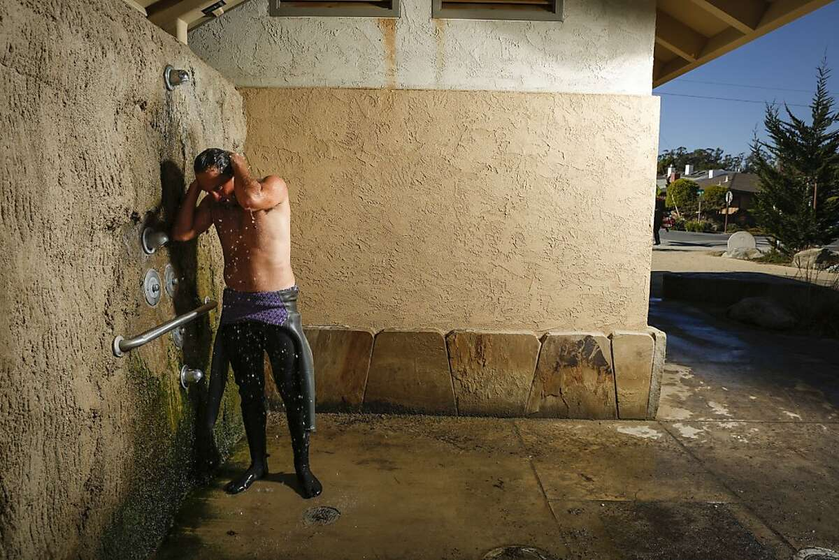 Shawn Dollar showers off after being in the water on Tuesday, Nov. 12, 2013 in Santa Cruz, Calif.