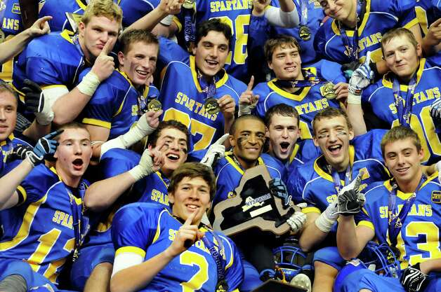 Queensbury teammates pose with the plaque as they celebrate their 36-7 win over Williamsville North in the Class A state football final on Friday, Nov. 29, 2013, at the Carrier Dome in Syracuse, N.Y. (Cindy Schultz / Times Union) Photo: Cindy Schultz / 00024836A