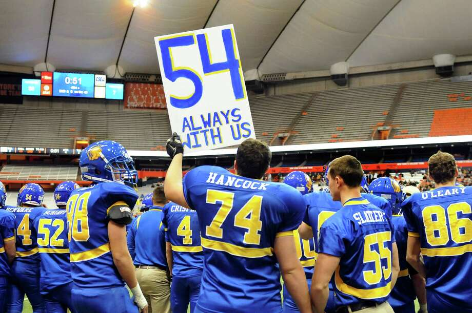 Queensbury's Tyler Hancock, center, holds the number of a teammate, Johnathan Vasiliou, as the team celebrates their 36-7 win over Williamsville North in the Class A state football final on Friday, Nov. 29, 2013, at the Carrier Dome in Syracuse, N.Y. Vasiliou died suddenly last year at the age of 16. (Cindy Schultz / Times Union) Photo: Cindy Schultz / 00024836A