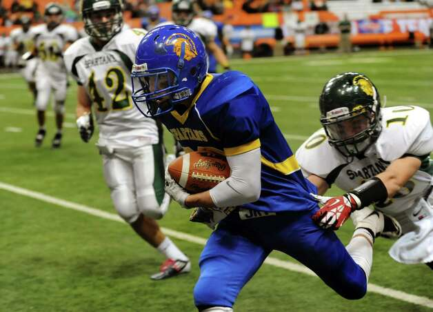 Queensbury's Kody Bruno, center, gains yards as Williamsville North's Dean Thompson, right, defends during their Class A state football final on Friday, Nov. 29, 2013, at the Carrier Dome in Syracuse, N.Y. (Cindy Schultz / Times Union) Photo: Cindy Schultz / 00024836A