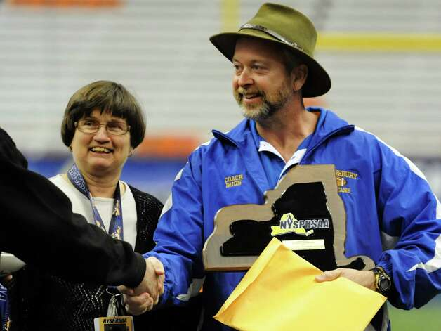 Queensbury's coach John Irion, right, receives the team plaque after winning 36-7 over Williamsville North in their Class A state football final on Friday, Nov. 29, 2013, at the Carrier Dome in Syracuse, N.Y. (Cindy Schultz / Times Union) Photo: Cindy Schultz / 00024836A