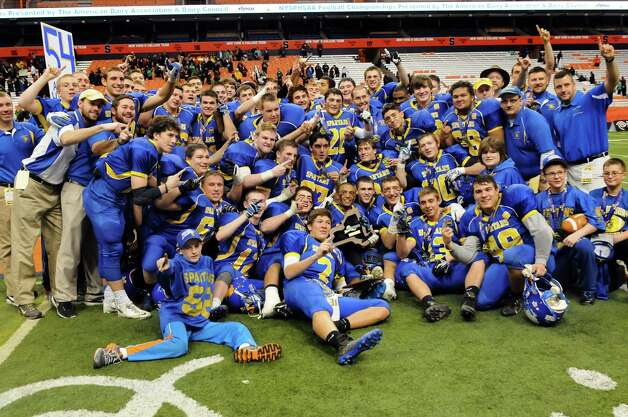 Queensbury players, coaches and staff pose  with the team plaque after winning 36-7 over Williamsville North in their Class A state football final on Friday, Nov. 29, 2013, at the Carrier Dome in Syracuse, N.Y. WEB ONLY (Cindy Schultz / Times Union) Photo: Cindy Schultz / 00024836A