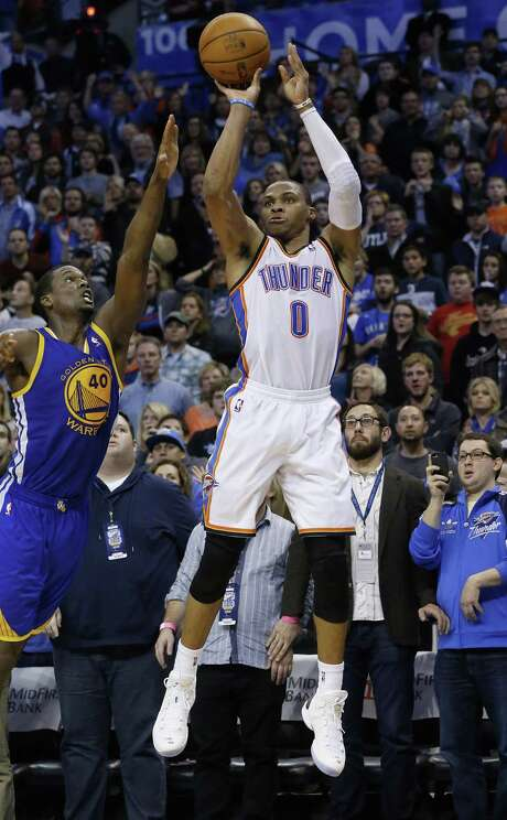 Russell Westbrook lets his game-winning shot fly over Harrison Barnes in overtime. The 3-pointer gave Oklahoma City a victory over visiting Golden State. Photo: Sue Ogrocki / Associated Press