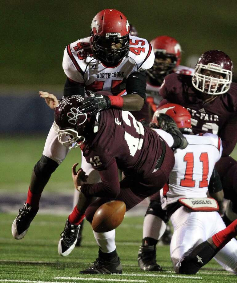 Cy-Fair's Drew Tobler, left, fumbles the ball after being tackled by North Shore's Zack Whitley (45) during the first half of a high school football playoff game, Friday, November 29, 2013, at Tully Stadium in Houston. Photo: Eric Christian Smith, For The Chronicle