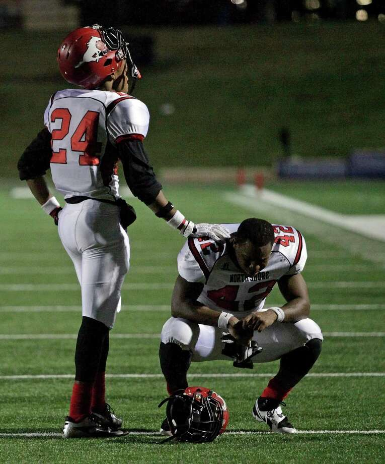 North Shore's Bryce Alley, left, consoles teammate Christian Jacobs after the Mustangs' 9-7 defeat to Cy-Fair in a high school football playoff game, Friday, November 29, 2013, at Tully Stadium in Houston. Photo: Eric Christian Smith, For The Chronicle