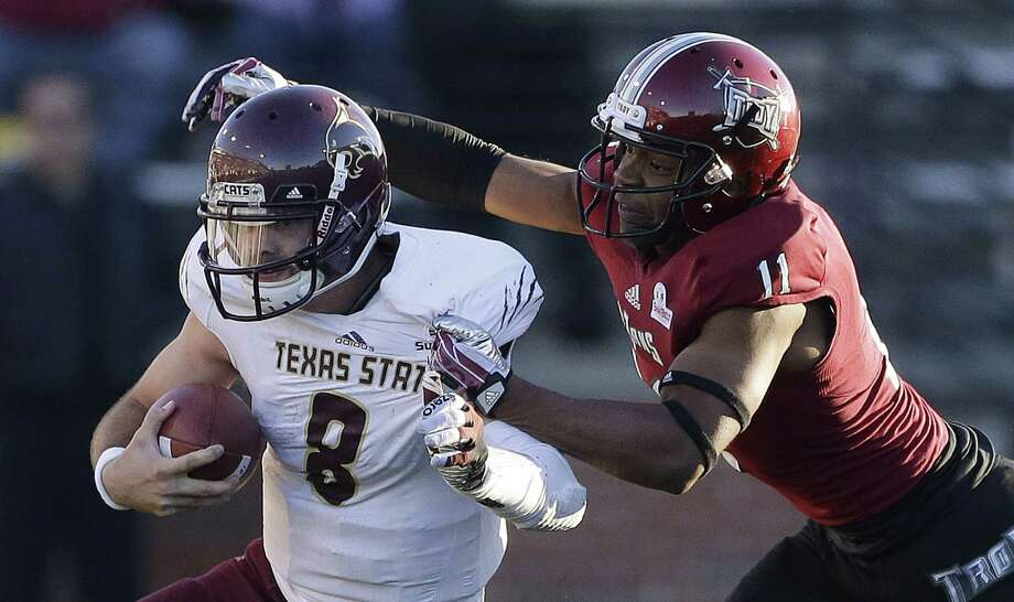 Texas State quarterback Duke DeLancellotti (left) is taken down by Troy safety Jeremy Spikner in Troy, Ala. Photo: Dave Martin / Associated Press