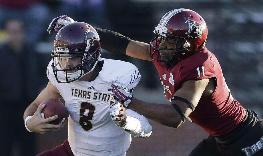 Texas State quarterback Duke DeLancellotti (left) is taken down by Troy safety Jeremy Spikner in Troy, Ala. Photo: Dave Martin / Associated Press
