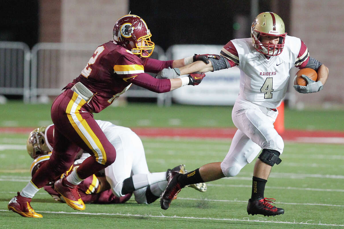 Harlandale's Damien Avina (left) tries to hold onto Leander Rouse quarterback Billy Ray McCrary during the third quarter of their Class 4A Division I third round playoff game at Bobcat Stadium in San Marcos on Friday, Nov. 29, 2013.