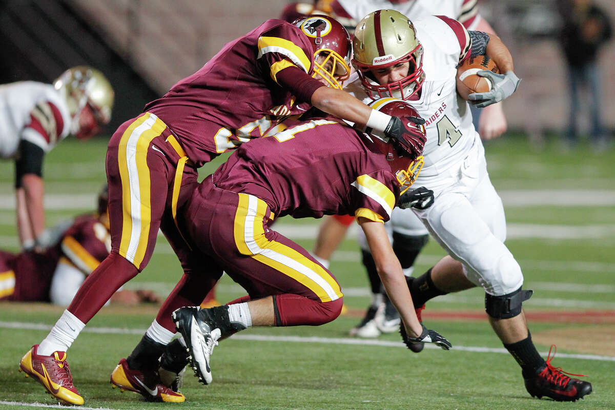 Harlandale's Ruben Zavala (left) and Ramzey Martinez combine to bring down Leander Rouse quarterback Billy Ray McCrary (right) during the third quarter of their Class 4A Division I third round playoff game at Bobcat Stadium in San Marcos on Friday, Nov. 29, 2013.