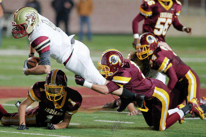 Harlandale's Ruben Zavala (bottom right) tackles Leander Rouse quarterback Billy Ray McCrary during the third quarter of their Class 4A Division I third round playoff game at Bobcat Stadium in San Marcos on Friday, Nov. 29, 2013. Leander Rouse beat Harlandale 43-21.
