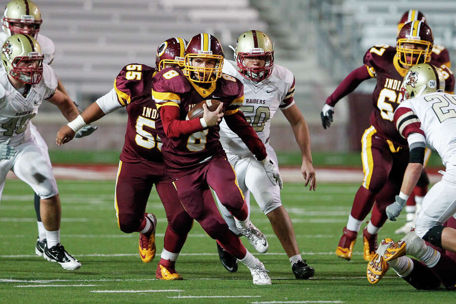 Harlandale's Eddie Pedroza (center) picks up yardage on a third quarter reception during the Indians' Class 4A Division I third round playoff game with Leander Rouse at Bobcat Stadium in San Marcos on Friday, Nov. 29, 2013. Photo: MARVIN PFEIFFER, Marvin Pfeiffer/ Express-News / Express-News 2013